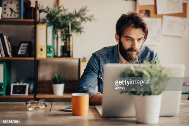 Young self employed writer working on laptop