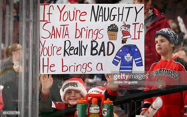 A young Senators fan holds a sign showing there are worse things than being on Santa's naughty list prior to a game between the Ottawa Senators and...