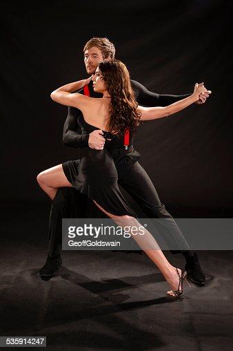sensual joven pareja bailando el tango aislado en negro : Foto de stock