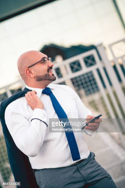 Young Serious Businessman Leaving Work After Busy day With Jacket on Shoulder