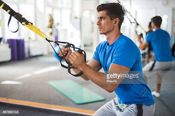 Young serious man exercising on Pilates class in health club.