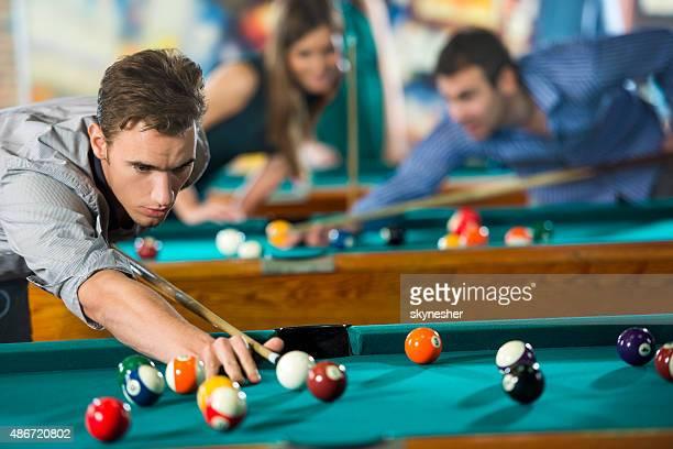 Young serious man playing billiard.