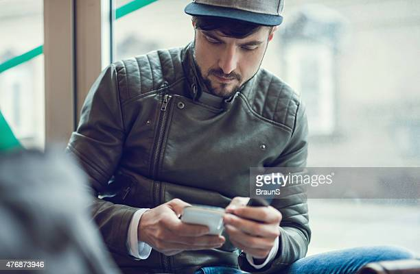 Young serious man using two cell phones.