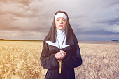 Young serious nun with cross on wheat field background