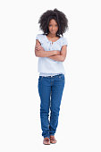 Young serious woman crossing her arms against a white background