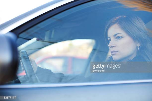 Young serious woman is driving a car.