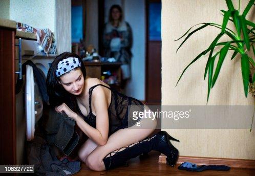 Giovane ragazza sessuale nascondere abiti maschili in lavatrice : Foto stock