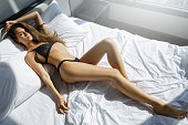 Young and sexy woman wearing black lingerie is lying on the bed