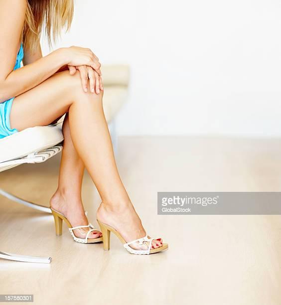 Junge sexy Frau in high heels auf einer couch