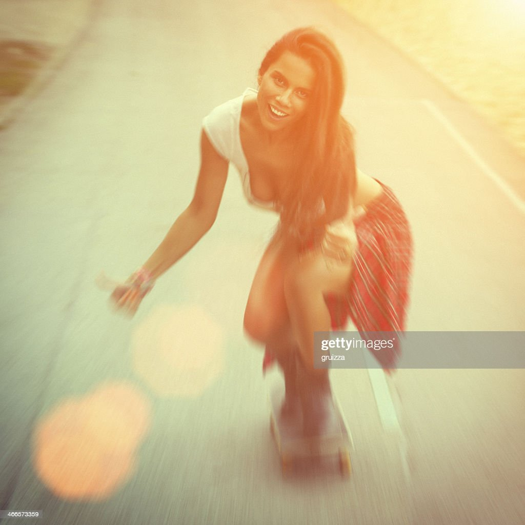Young sexy woman in jeans riding a skateboard with smile