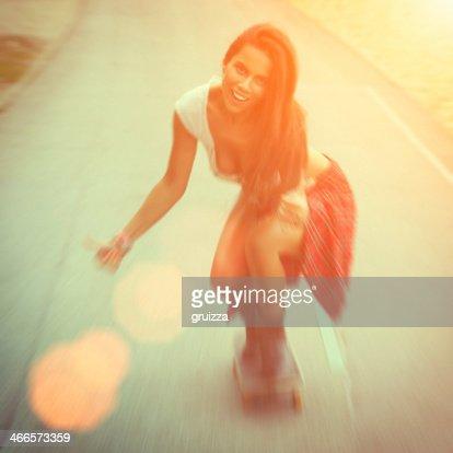 Jeune sexy femme en jeans équitation un skate avec le sourire