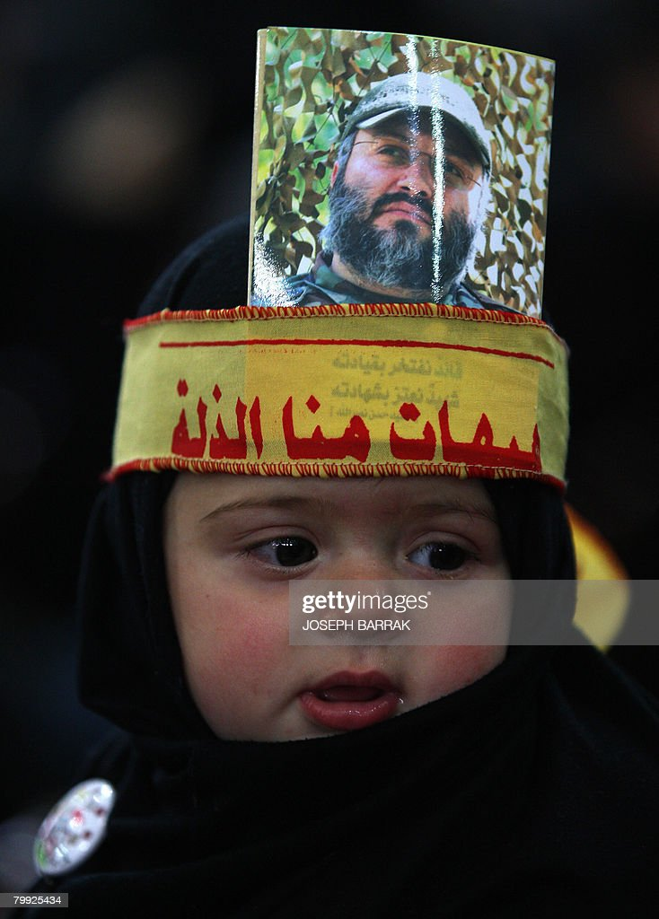 A young Shiite Muslims girl wears a black head dress adorned with an image assassinated top Hezbollah commander Imad Mughnieh as she and her family...