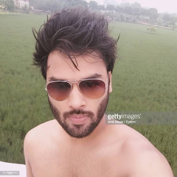 Young Shirtless Man Wearing Sunglasses On Agricultural Field