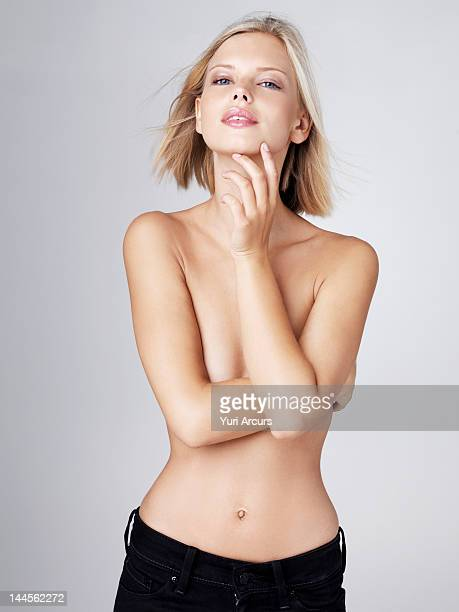 Young shirtless woman with arms covering breasts, studio shot
