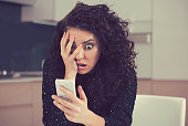 Young shocked anxious woman looking at phone seeing bad news photos message with scared emotion on face