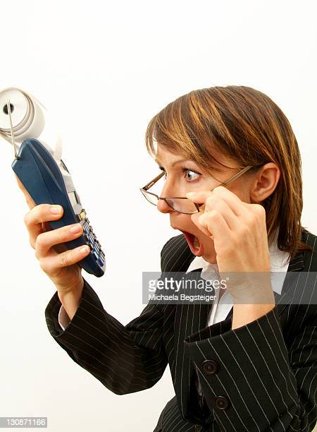Young, shocked business woman with pocket calculator