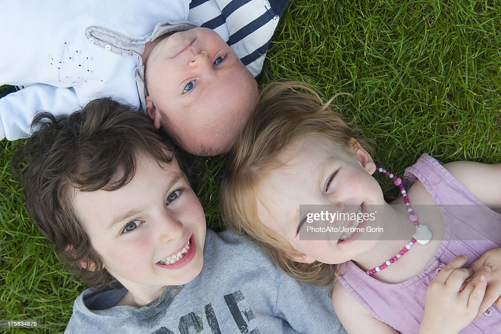 Young siblings lying on grass, portrait