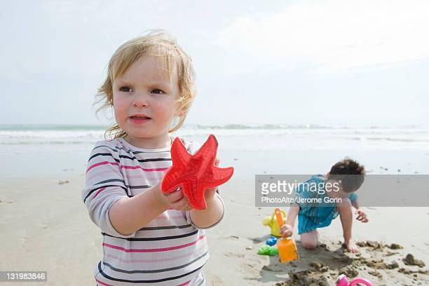 Young siblings playing in sand at the beach