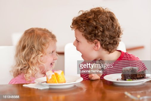 Young siblings sitting at table with cake : Stock Photo