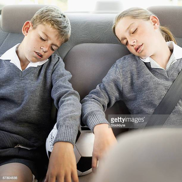 Young siblings sleeping in school uniform inside a car
