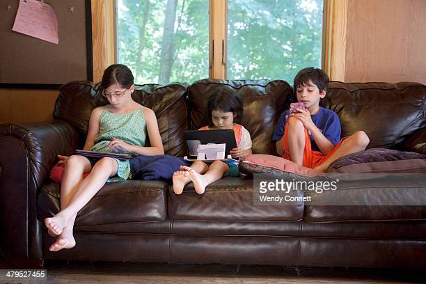 Young siblings using electronic devices