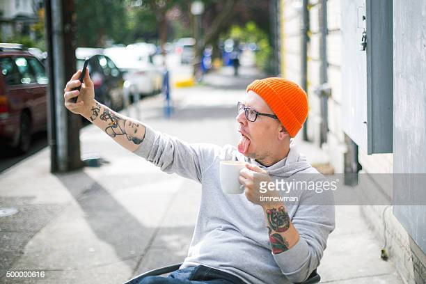 Young Silly Man Drinking Coffee and Taking Selfie