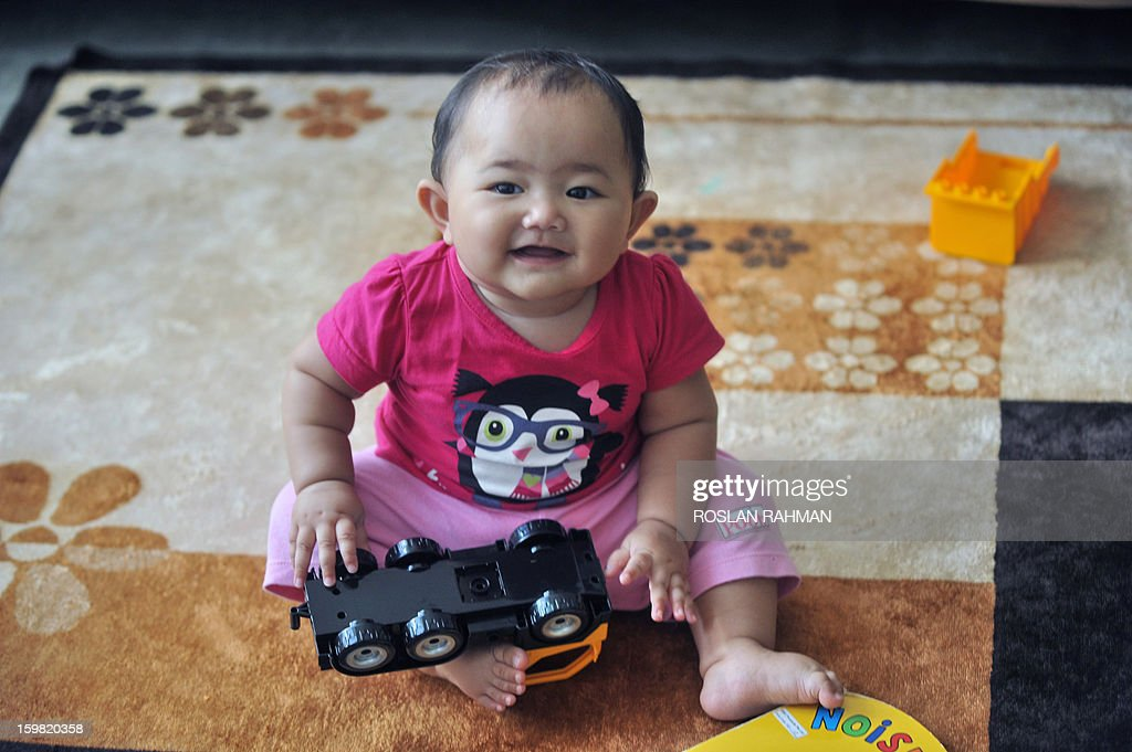 A young Singaporean baby plays at her home in Singapore on January 21, 2013. Singapore on January 21 announced increased cash bonuses for parents of newborn babies and introduced paternity leave as part of a package of measures to boost population and reduce dependence on foreigners.