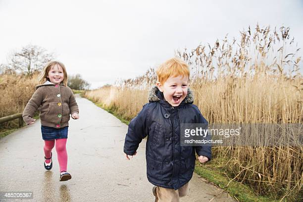 Young sister and brother racing along rural road