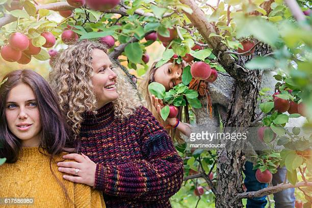 Young sister bombing mother and daughter portrait in orchard.