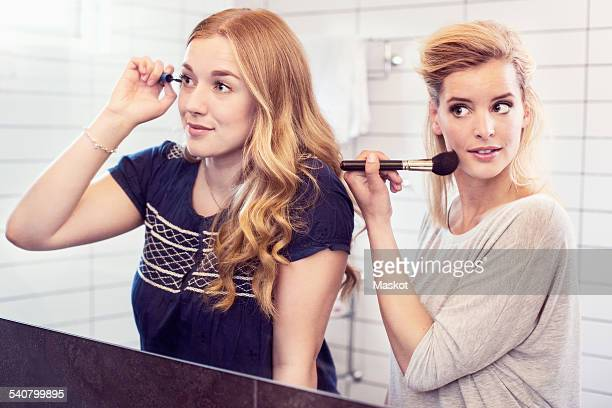 Young sisters applying makeup in mirror