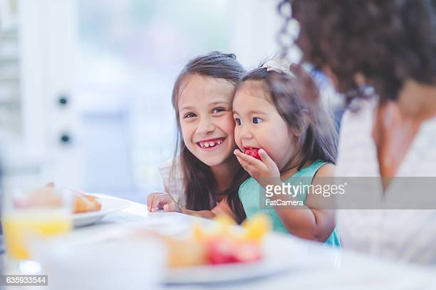 Young sisters eating breakfast in the kitchen smiling at camera