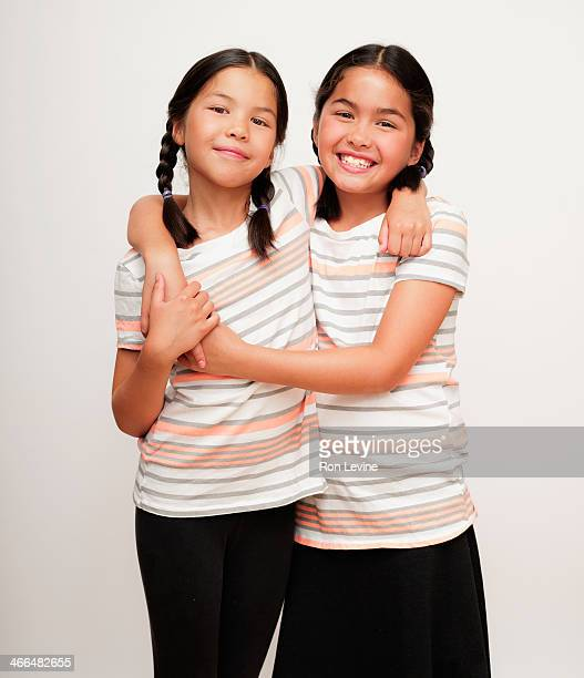 Young sisters in braids, hugging