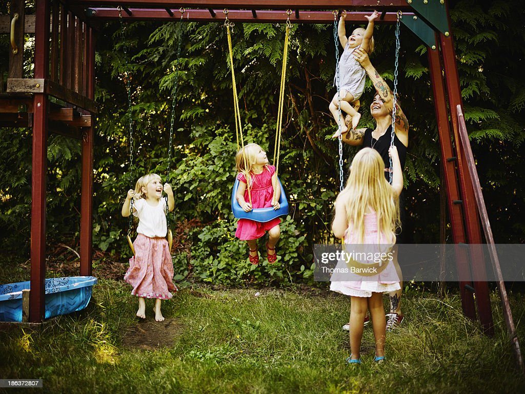 Young sisters on swings and mother holding toddler : Stock Photo