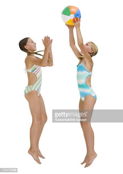 Young sisters on vacation playing with a beach ball