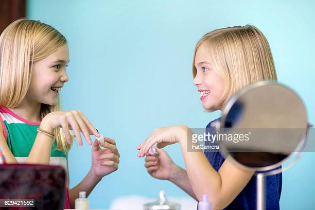 Young sisters painting their nails together for dress