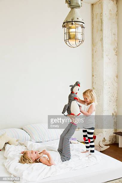 Young sisters playing with soft toy on the bed