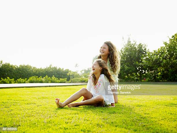 Young sisters sitting on grass laughing