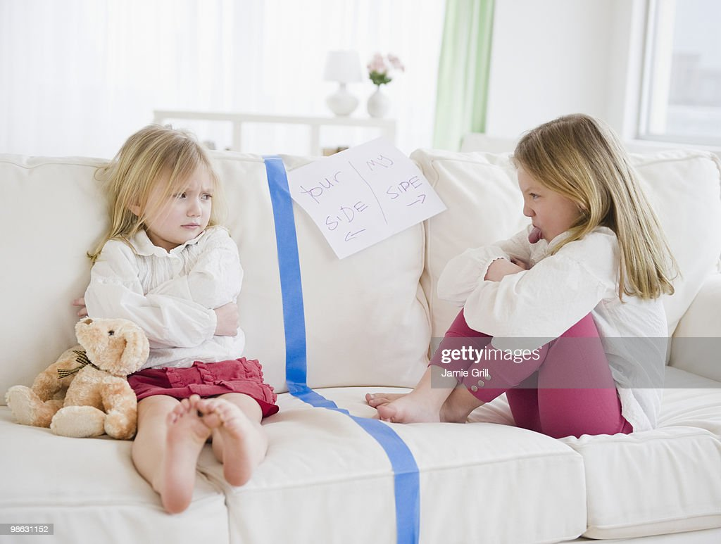 Young sisters sitting on opposite sides of couch
