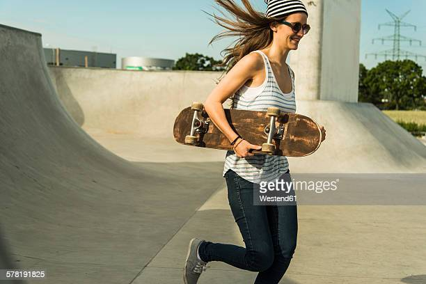 Young skate boarder running in a skatepark