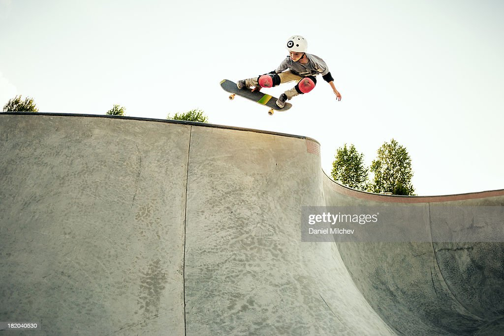 Young skateboarder jumping at a skate park.