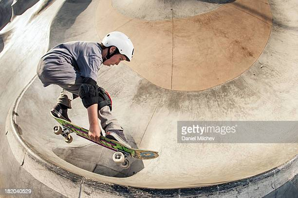 Young skateboarder jumping over an opening.