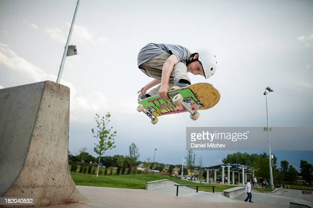Young skateboarder riding at a skate park.