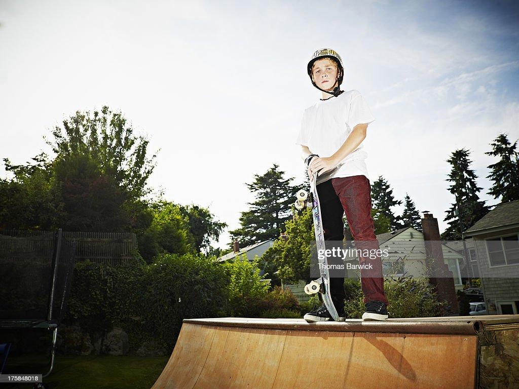 young skateboarder standing on backyard halfpipe stock photo