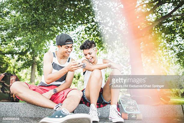Young skateboarding couple sitting on park wall looking at smartphone