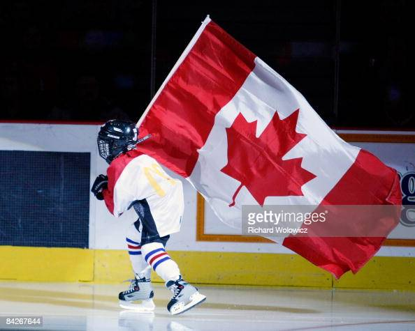 A young skater carries the Canadian flag during pregame ceremonies before the game featuring Team Canada versus Team Czech Republic at the IIHF World...