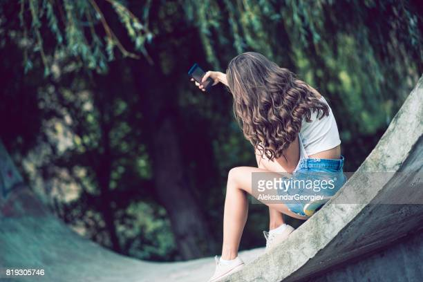 Young Skater Girl Sitting on Board Taking Selfie In Public Skateboard Park