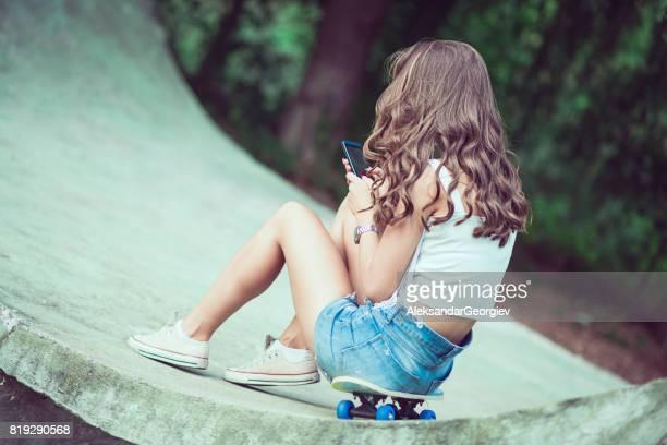 Young Skater Girl Surfing The Net In Public Skateboard Park