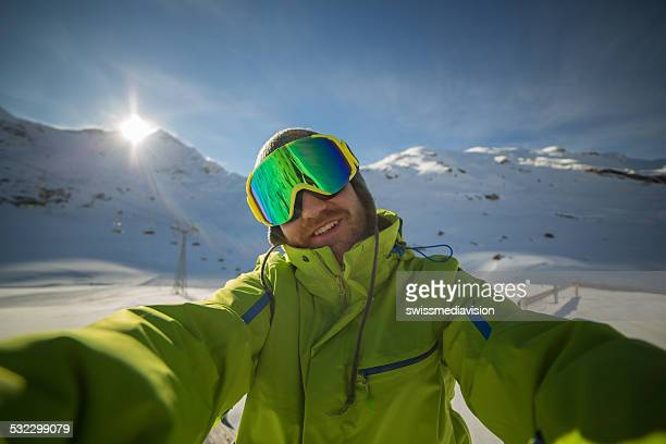 Young skier man taking selfie on ski slopes-Sunset time