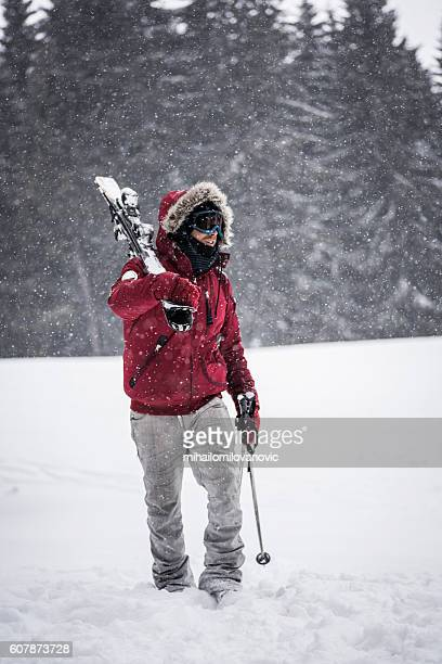 Young skier walking through snow storm