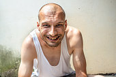 Happy smiling homeless man, Young skinny anorexic bald positive and happy smiling homeless man sitting on the urban street in the city or town near white wall with big smile looking at the camera, hom